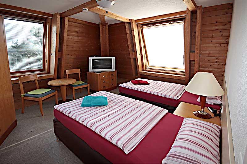 Zweibettzimmer mit Betten, TV, Schrank und Sitzgruppe Pension Bianca