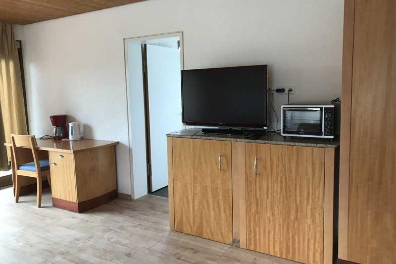 Ausstattung mit TV im 3-Bett-Zimmer des Boardinghouses